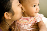 Asian mother kiss baby — Stock Photo