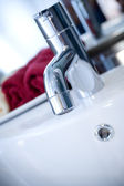 Clean luxurious washbasin tap with red towels — Stock Photo