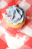 Cupcake on red table cloth — Stock Photo
