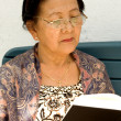 Aisan elderly woman reading a book — Stock Photo