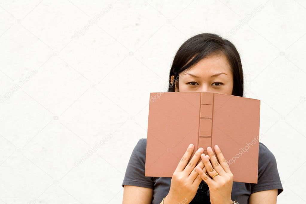 Book Covering Face : Girl face cover with book — stock photo ampyang