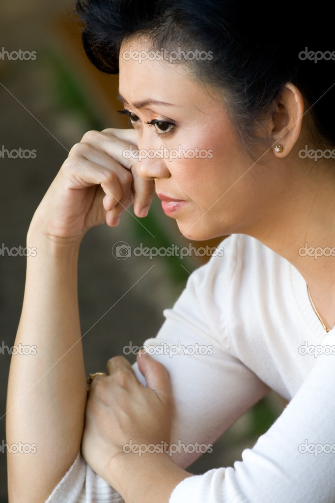 Portrait of asian ethnic mature woman in sorrow having a serious thought of ...