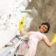 Strong woman painting wall — Stock Photo