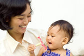Asian working mother palying with baby — Stock Photo