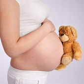 Teddy Bear and Pregnant Belly — Stock Photo