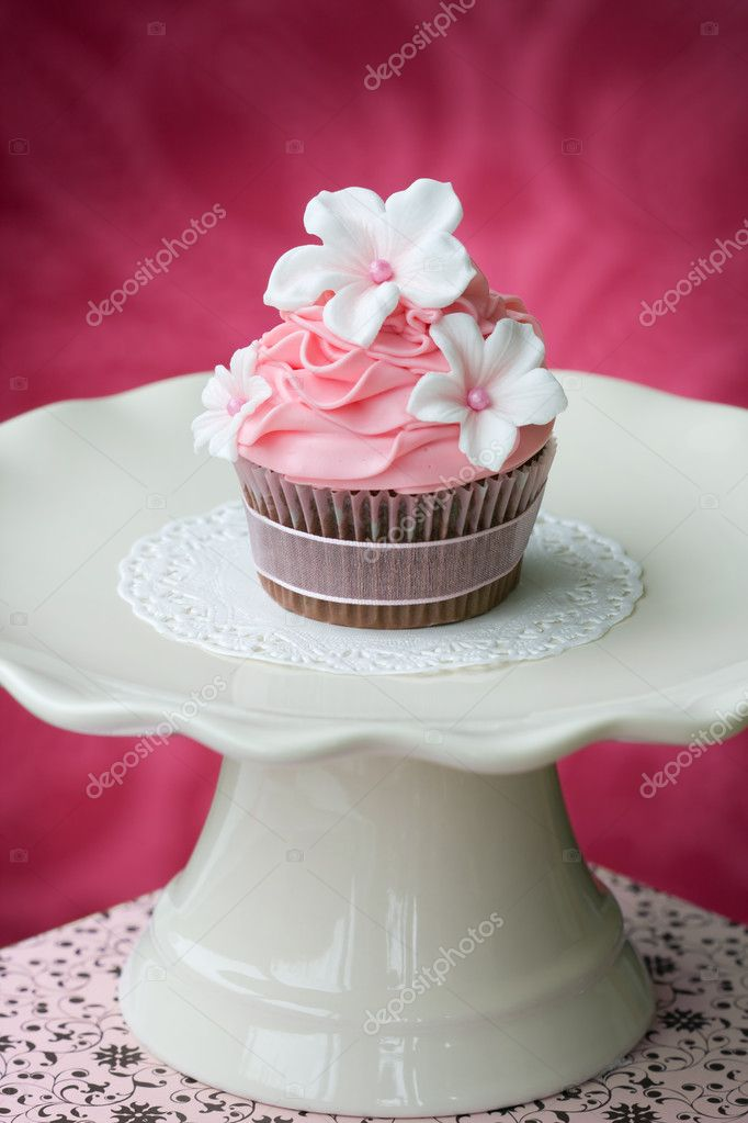Pink cupcake on a cream colored cakestand — Stock Photo #3250839