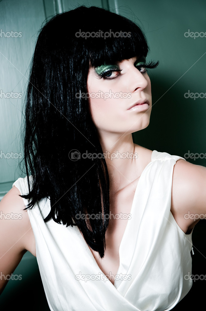 Brunette with heavy makeup posing in front of a green wall — Stock Photo #2716772
