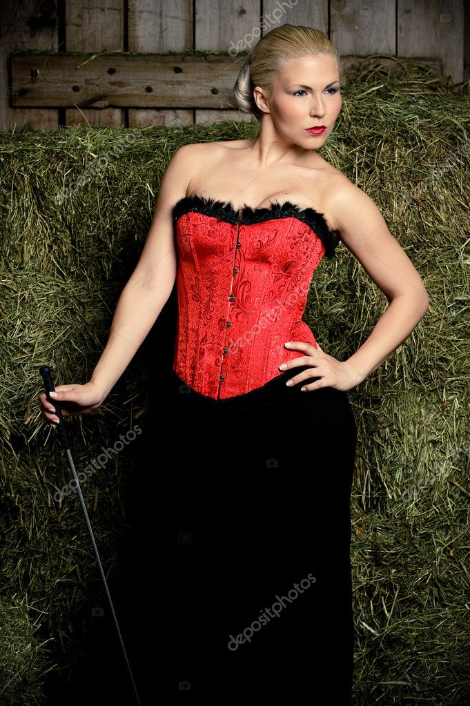 A lady wearing a red corset in a stable — Stock Photo #3352278