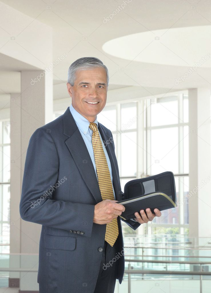 Smiling middle aged businessman holding a planner notebook. Man is standing in the atrium of a modern office building. Vertical format. — Stock Photo #3600613