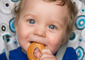 Baby boy with bread ring — Stockfoto