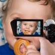Foto Stock: Baby boy recording to camcorder