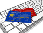 Credit cards on a computer keyboard — Stock Photo