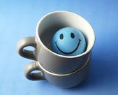 Taza azul con cara de juguete — Foto de Stock