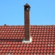 Red brick chimney on tile roof - Stock Photo