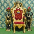 Vintage luxury throne chair with two egyptian statues — Stock Photo