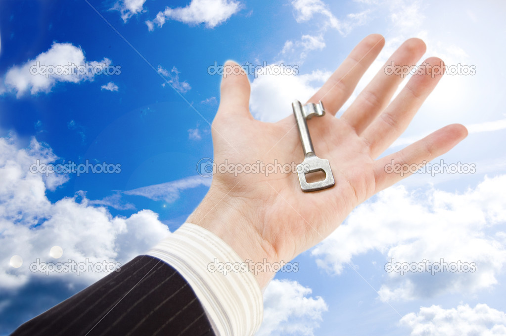 Key to success conceptual image. The businessman holds the key to success againts the blue sky. — Stock Photo #2762406
