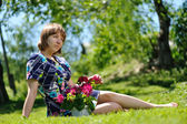 Attractive girl sitting on the grass — Stock Photo