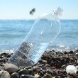 Stock Photo: Bottle of water on beach of sea