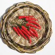 Red chili peppers on a wicker stand — Stock Photo