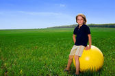 Boy with ball in field — Stock Photo