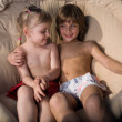 Girl and boy in an armchair - Stock Photo