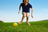 Cheerful boy with ball in field — Stock Photo