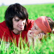 Long-haired girl with boy on grass — Stock Photo #3361537