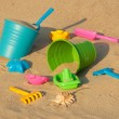 Colorful plastic toys on the sandy beach — Stock Photo