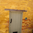Door to a yellow brick house - Stock Photo