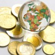 World globe and different coins — Stock Photo