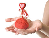 Hands with red ball of threads and heart — Stock Photo