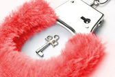 Red fluffy handcuffs — Stock Photo
