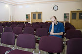 Boring lecture. Alone sleeping student in empty auditorium — Stock Photo