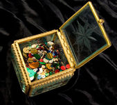 Little box with color beads on black velvet — Stock Photo