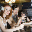 Retro girlfriends at bar with wineglasses — Stock Photo