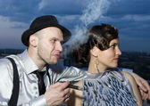 Smoking impudent gangster with retro girl — Stock Photo