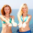 Stock Photo: Two women in bikini inviting to sea