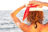 Woman in christmas hat looking at the sea — Stock Photo