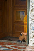 Beggar at church door — Stock Photo
