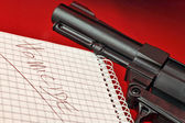 Close-up of a notepad with word 'homicide' and gun on red background with selctive focus — Stock Photo