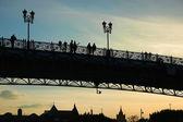 Silhouettes on bridge at sunset — Stock Photo