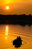Fishermen in boat at sunset — Stock Photo