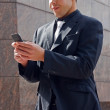 A business man sending a message on his mobile phone. — Stock Photo #3626843