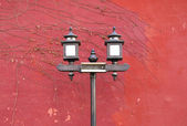 Old style lamp with red wall — Stock Photo
