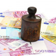 Stock Photo: Old rusty cast-iron weight and money