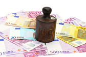 Old rusty cast-iron weight and money — Stock Photo