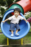 Boy standing on a slide — Stock Photo