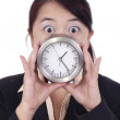 Shocked businesswoman with clock — Stock Photo