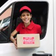 Delivery courier in truck handing over package - Stock Photo