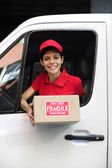Delivery courier in truck handing over package — Stok fotoğraf